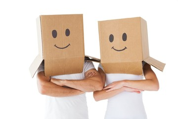 Couple wearing smiley face boxes on their heads