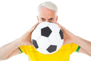 Brazilian football fan in yellow holding ball