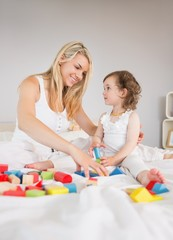 Mother and daughter playing with building blocks on bed