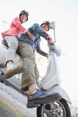 Happy senior couple riding a moped