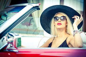 Outdoor summer portrait of stylish blonde vintage woman driving