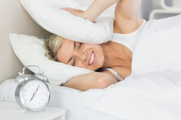 Woman covering ears with pillow and alarm clock in foreground