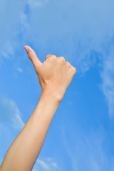 Closeup  hand thumbs up sign blue sky background