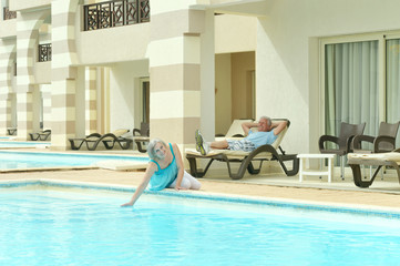 Elderly couple relaxing by pool
