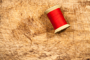 wood Background with sewing tools and colored thread.