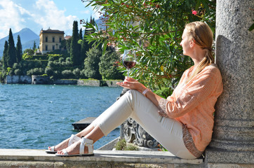 Girl with a glass of wine at the villa Monastero. Lake Como, Ita