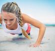Woman doing push-ups on the beach.