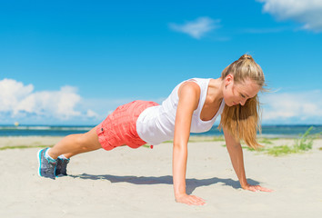 Woman doing push-ups on the beach.