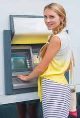 Pretty woman withdrawing money from an ATM.