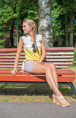 Beautiful young woman sitting on the bench.
