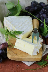 Soft brie cheese with sweet grapes on a wooden board