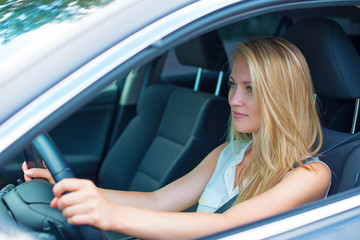 Beautiful young woman driving a car.