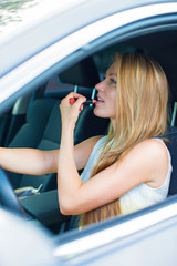 Beautiful young woman applying make-up while driving car.