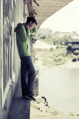 Young man in depression standing on the river bridge