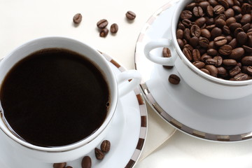 Black coffee and coffee beans in a cup
