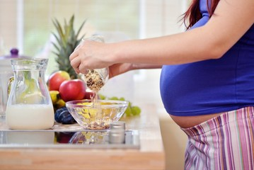 pregnant woman prepering meal