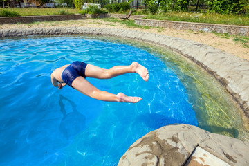 Teenager jumping into pool