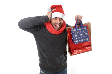young stressed man wearing santa hat holding red shopping bags