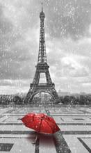 Wieża Eiffla w deszczu. czarno-białe zdjęcie z czerwonym elementem