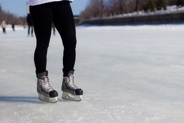 A pair of legs with ice skates on the ice during winter