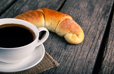 Coffee cup with a croissant breakfast