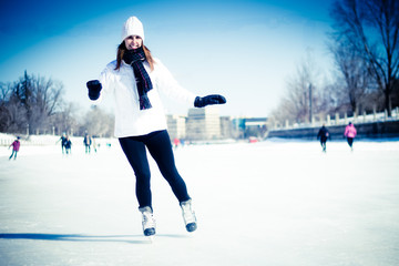 Attractive young woman ice skating during winter - blue filter a