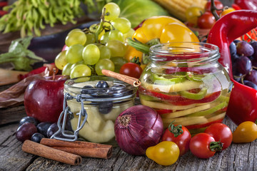 canned pepper and pear with autumn fruits and vegetables around
