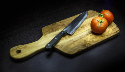 Chopping board with two tomatoes