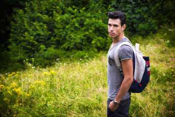 Handsome athletic young man with backpack at mountains