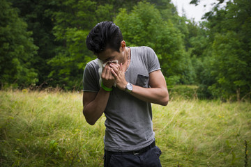 Young man outdoors sneezing in handkerchief
