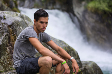 Handsome young man near mountain waterfall on rocks