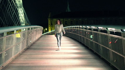 Young woman walking through the bridge in the city