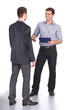 Leinwanddruck Bild - Two business men shaking hands and one of them holding a folder