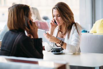 Multi ethnic businesswomen talking on phone and using tablet com
