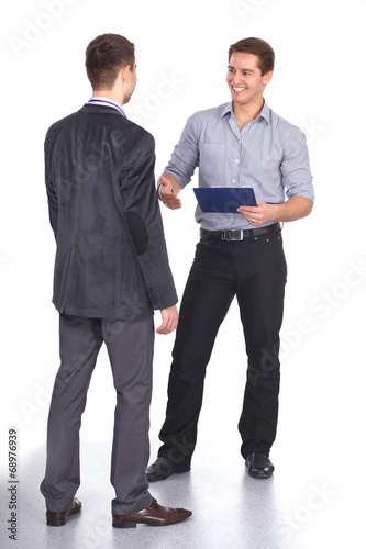 Leinwanddruck Bild Two business men shaking hands and one of them holding a folder