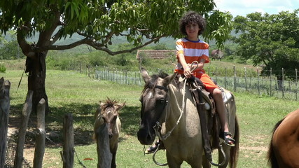Child riding a horse in the countryside
