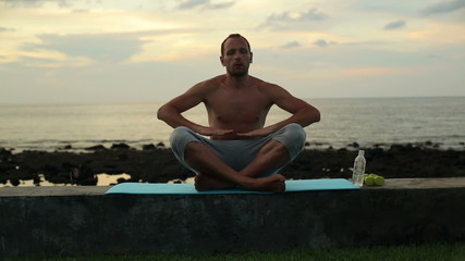 Man doing breathing exercise by the sea in the evening