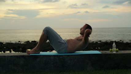 Man exercising, doing sit ups by the sea in the evening