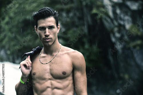 canvas print picture Young man near mountain waterfall with shirt on shoulder