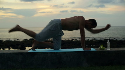 Man exercising, stretching spine by the sea in the evening