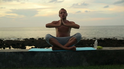 Man meditating by the sea in the evening