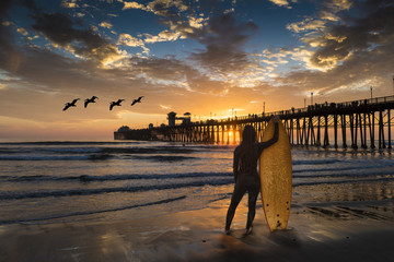 A female surfer admires a sunset near the Oceanside Pier.