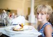 Child girl eating ice cream in restaurant