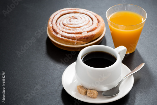 black coffee, sweet bun and orange juice on a black background - 68982784