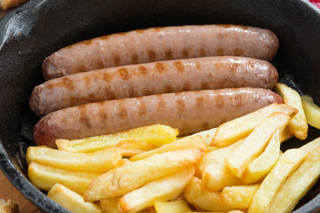 grilled sausages with French fries in a frying pan, close-up