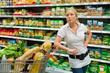 Frau mit Einkaufswagen im Supermarkt
