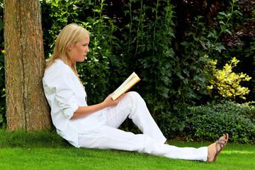 Frau liest Buch im Park