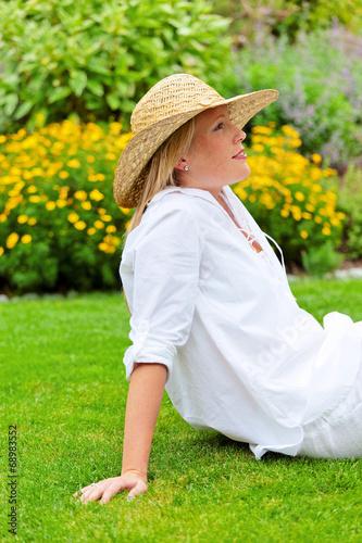 Frau sitzt zur Erholung in einer Wiese