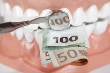 Demo Gebiß mit Geldscheinen und Zahnarztspiegel