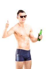 Man in swim shorts holding a beer and giving thumb up